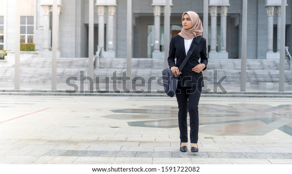 Cute Asian Malay Lady walking at hallway wearing suit and hijab