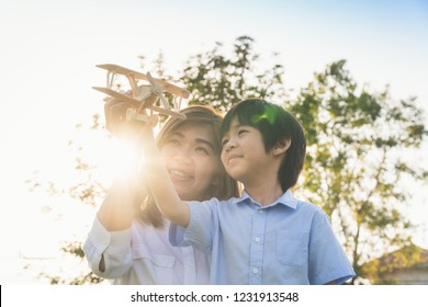 Cute Asian mother and son playing wood airplane together in the park outdoors