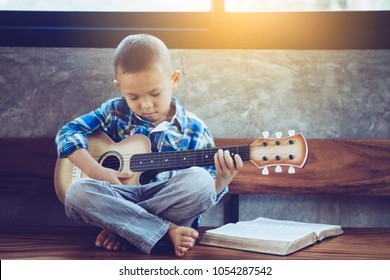 cute Asian praying while holding small guitar with bible on wooden chair in the office