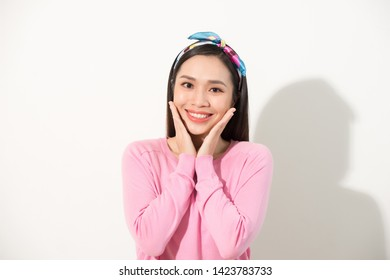 Cute asian presenting her face with hands touching face in v shape, portrait, skincare and cosmetic concept, pink shirt, white background