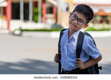 A cute Asian primary school boy wearing glasses and a white school uniform, carrying a black backpack, standing in front of the school.