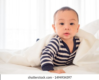 cute asian seven-month baby in white dress smiling with his mother in bedroom at home