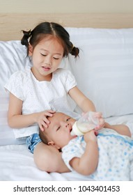 Cute Asian sister feeding milk from bottle for her brother and lying on the bed.