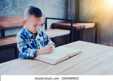 cute asian small boy praying over open bible on wooden table