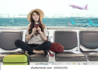 Cute asian student college traveler feeling happy action with travel plan and waiting for flight at airport terminal. Teenager travel concept