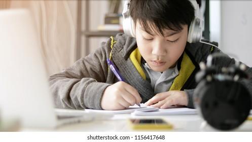 Cute asian teen boy doing your homework at home.