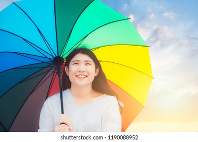 Cute Asian teen happy smile outdoor with rainbow colorful umbrella sunny day