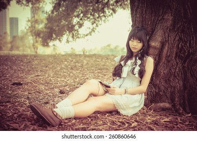 A cute Asian Thai girl is leaning on a tree trunk sleeping while listening to the music with earphone on tablet