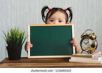 cute asian toddler holding a blank chalkboard for copy space text. Concept of early education and child growth