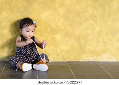 cute asian toddler try to wear her own brown shoes. toddler tries to tie her own shoelace. put on your own shoes day