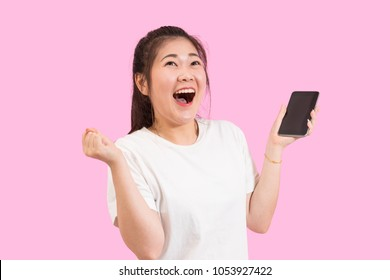 Cute asian woman holding smart phone in hand, screams with joy and happiness, suprise feeling, winner expression, white shirt, pink background