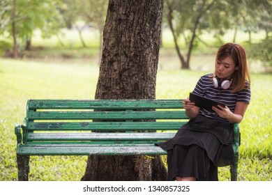 Cute Asian woman sit on green chair in summer park to work on digital tablet. People lifestyle and technology concept. Nature and relaxation theme.