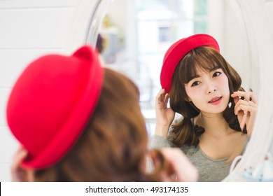 Cute Asian woman sitting at the dressing table on the bedroom - lifestyle and people concept