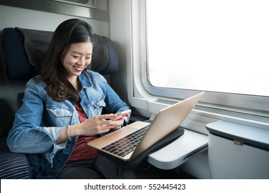 Cute Asian woman smiling at smartphone with laptop on train, copy space on window, business travel or communication technology concept