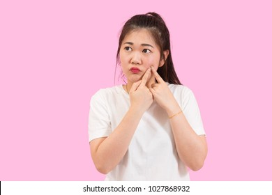 Cute asian woman squeezes her acne, skin problem, unhappy feeling, white shirt, pink background
