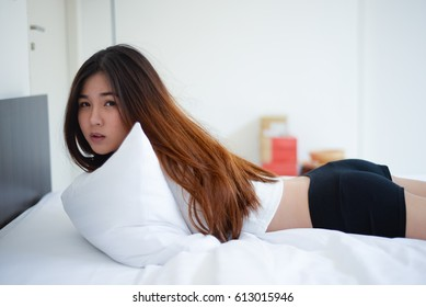 cute asian woman in white shirt on bed