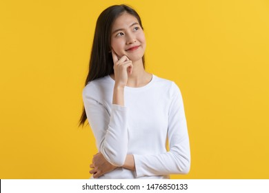 Cute asian young woman in white casual shirt looking up and thinking / imagination isolated on yellow background in studio.
