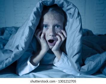 Cute asleep girl screaming and crying after frightening or upsetting dream covering herself with blanket in bed at night in mood dramatic lighting in Sleep terrors Nightmares and Sleeping disorders.