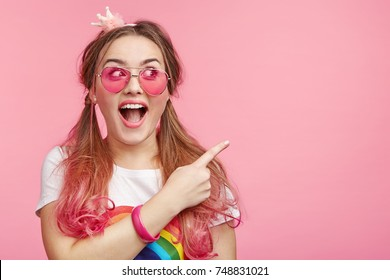 Cute astonished young female with pony tails and pink hair tips, points at copy space with fore finger advertises something, keeps mouth widely opened. People, advertising, surprisment concept