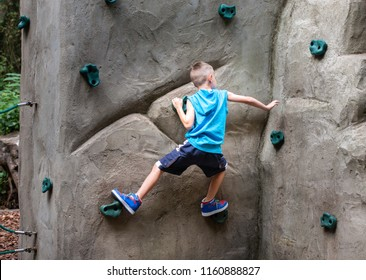 A cute athletic little boy practices his climbing skills on a little climbing wall in Colchester Public Country Park