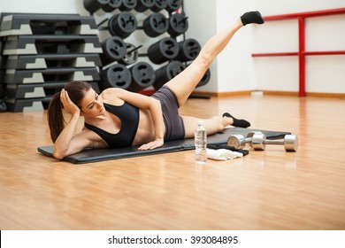 Cute athletic young woman doing side crunches to work on her abs at the gym