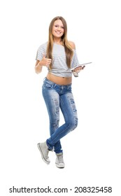 Cute attractive Caucasian teenage girl with digital tablet. Casual styled young teen woman in blue jeans and gray shirt smiling holding tablet pc gesturing thumbs us. White background.