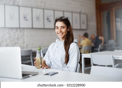 Cute attractive european young woman sitting in front of laptop, wearing trendy sweatshirt and stylish glasses, drinking beverage while in cafe. Freelancer took break from work, sipping cocktail.