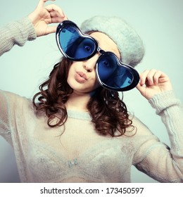 Cute attractive fashion young girl posing at studio with funny big love glasses and gives kisses, toned