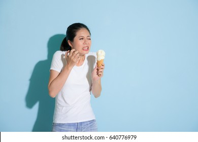 cute attractive female student after eating delicious ice cream feeling sensitive teeth painful uncomfortable and making sadness expression in blue wall background.