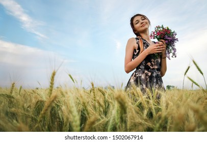 Cute attractive girl with a bouquet of colorful flowers in her hands. Young woman breathes in the scent of plants on wheat field during sunset. Pensive look. Romantic atmosphere.