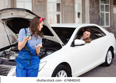 Cute attractive girl examining car engine at the auto repair shop