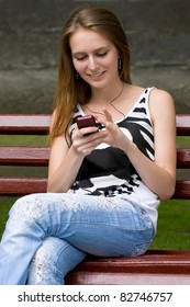 cute attractive girl is listening music in earphones plugs on mp3 player or mobile phone