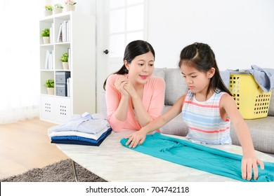 cute attractive little girl learning folding clothing when mother looking at her and explaining organized method for her.