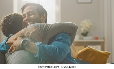 Cute Attractive Male Gay Couple Sit Together on a Sofa at Home. Boyfriends are Hugging and Embracing Each Other. They are Joyful and Laughing. They are Casually Dressed and Room Has Modern Interior.
