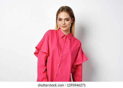 cute attractive woman in a pink shirt on a light background
