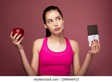 Cute attractive young girl athlete in a pink sports top holds a red apple and chocolate in her hands. Pensive fitness lady holds a red apple and chocolate in her hand on a pink background.
