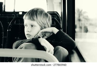 Cute autistic boy siting in empty bus