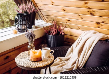 Cute autumn hygge home decor arrangement. Tiny wooden cabin balcony with heather flowers, lavender in bottle vase, candlelight flame, soft beige plaid waiting on comfortable garden furniture chair.