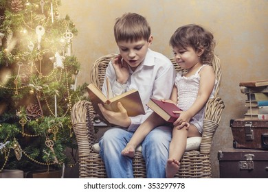 Cute babies boy and girl in a chair reading a book in a Christmas retro interior