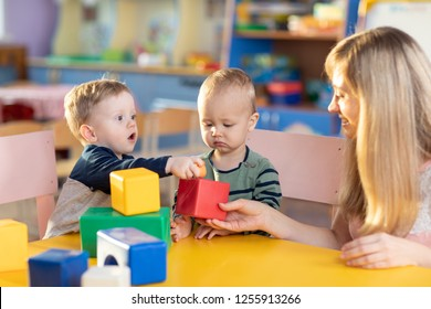 Cute babies play with blocks. Educational toys for preschool and kindergarten child. Little boys and educator build block toys at playroom or daycare. Education concept.