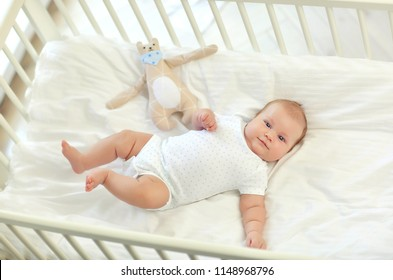 Cute baby 2 months lying in his crib with a toy