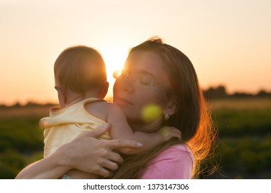 Cute baby in the arms of a happy mother in the rays of the setting sun. The concept of a good family.