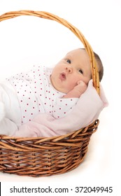 Cute baby in basket. Looking at camera