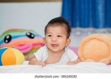 Cute baby in bed smiling and looking at camera.