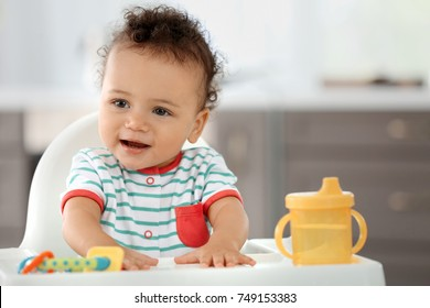 Cute baby with bottle of water sitting in kitchen