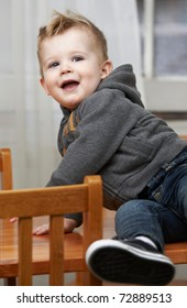 Cute baby boy at 18 months sitting on table at home.