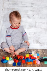 Cute baby boy with bare foot and plenty of colorful wooden bricks bsckground. Image with selective focus