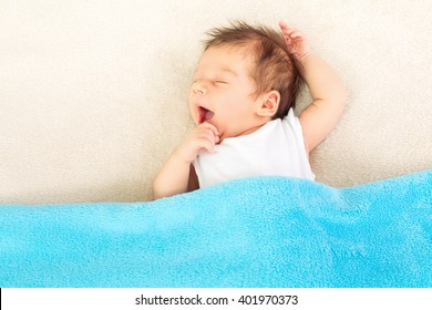 Cute baby boy in bed, covered with blue soft fleece blanket, yawning and sleeping. High angle view, copy space, mild retouch.