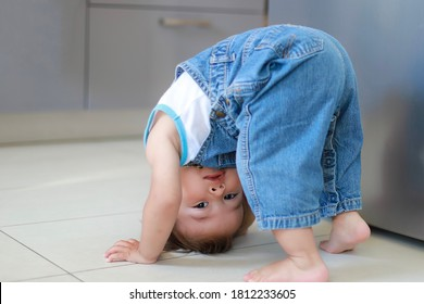 Cute baby boy bending over doing yoga at home. Mixed race Asian-German infant play and learning development. Happy and funny kid.