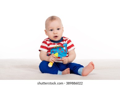 cute baby boy with big eyes sitting on a blanket. child about eight - ten month looks at the camera